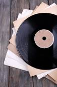 Vinyl records records and paper covers on wooden background — Stock Photo
