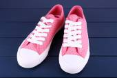 Pink trainers on dark blue wooden background — Stock Photo