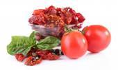 Sun dried tomatoes in glass bowl and basil leaves, isolated on white — Stock Photo