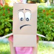 Woman with cardboard box on her head with sad face, outdoors — Stock Photo #52657559