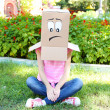 Woman with cardboard box on her head with sad face, outdoors — Stock Photo #52657583