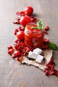 Sun dried tomatoes in glass jar, basil leaves and feta cheese on color wooden background — Stock Photo