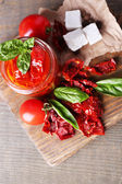 Sun dried tomatoes in glass jar, basil leaves and feta cheese on cutting board, on wooden background — Stock Photo