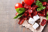 Sun dried and fresh tomatoes, basil leaves and feta cheese on color wooden background — Stock Photo