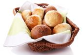 Tasty buns with sesame in wicker basket, isolated on white — Stock Photo
