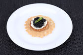 Black caviar with crispy bread on plate on dark fabric background — Stockfoto