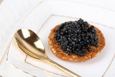 Black caviar on crispy bread on plate closeup — Foto Stock