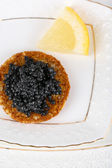 Black caviar on crispy bread on plate closeup — Stockfoto