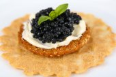 Black caviar with crispy bread on plate closeup — Foto Stock