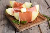 Delicious melon with prosciutto on table close-up — Stock Photo