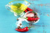 Set of spices and olive oil in glass sauce-boat, on color  wooden background — Stock Photo