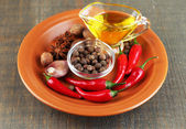 Set of spices and olive oil on plate, on  wooden background — Stock Photo