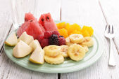 Sliced fruits and berries on plate with glass of water on wooden table — Stock Photo