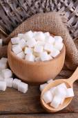 Refined sugar wooden bowl on table background — Stock Photo