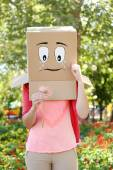 Woman with cardboard box on her head with sad face, holding flower, outdoors — Stock Photo