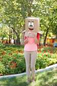 Woman with cardboard box on her head with happy face, holding flower, outdoors — Stock Photo