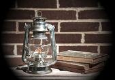Burning kerosene lamp and books — Stock Photo