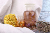 Bottles of herbal tincture and dried herbs on a napkin on wooden background in front of curtain — Stock Photo
