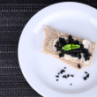 Slices of bread with butter and black caviar on plate on dark fabric background — Stock Photo #52701839