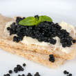 Slices of bread with butter and black caviar on plate closeup — Stock Photo #52701921