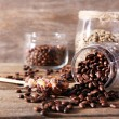 Glass jars and spoon with coffee beans on wooden table on wooden  background — Stock Photo #52702529