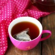 Cup of tea, teapot and tea bags on wooden table close-up — Stock Photo #52703463