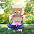 Woman with cardboard box on her head with sad face and ice cream on green grass, outdoors — Stock Photo #52703709