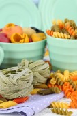Colorful pasta in color bowls and mugs on wooden background — Stock Photo