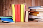 Libri sul tavolo di legno sullo sfondo della parete in legno — Foto Stock
