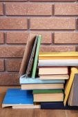 Books on wooden table on brick wall background — Stock Photo