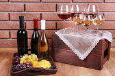 Bottles and glasses of wine, cheese and ripe grapes on table on brick wall background — Stock Photo
