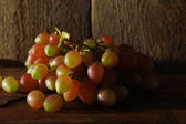 Pink grape on wooden table on wooden background — Stock Photo