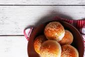 Tasty buns with sesame on plate, on color wooden background — Stock Photo