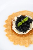 Black caviar with crispy bread on plate closeup — Stockfoto