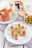 Delicious melon with prosciutto on plate on table close-up — Stock Photo