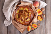 Delicious cake with peach and nuts on wooden table close up — Stock Photo