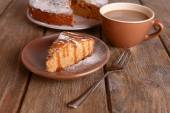 Delicious cake and cup of coffee on wooden table — Stock Photo