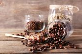 Glass jars and spoon with coffee beans on wooden table on wooden  background — Stock Photo