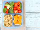Tasty vegetarian food in plastic box on wooden table — Foto Stock