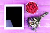 Tablet, field flowers and bowl — Stock Photo