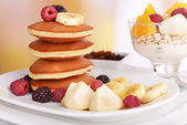 Pancake with fruits on plate and muesli on table on bright background — Stock Photo