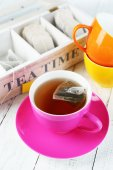 Cup with tea and tea bags on wooden table close-up — Stok fotoğraf
