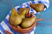 Ripe pears and cinnamon sticks in bowl, on color wooden background — Stock Photo
