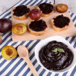 Bowl of plum jam, slices of bread with plum jam and fresh plums on cutting board on napkin on wooden background — Stock Photo #52794013