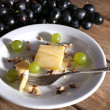 Tasty grape and cheese on plate, on wooden table — Stock Photo #52794103