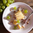 Tasty grape and cheese on plate, on wooden table — Stock Photo #52794109