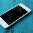 Modern mobile phone with broken screen on wooden background — Stock Photo #52794927