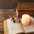Books, flowers and candle on napkin on wooden table on wooden wall background — Stock Photo