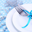 White plate, fork, knife and Christmas decoration on polka dot tablecloth closeup — Stock Photo #52795771