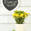 Yellow and green flowers in decorative jug on color wooden background — Stock Photo #52795907